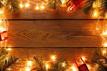 Image of wooden surface with burning garland around perimeter, branches of spruce, felt toys.