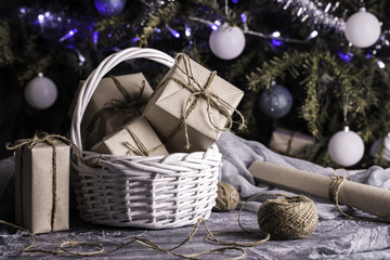 New Year's gifts in a white basket under a fir-tree