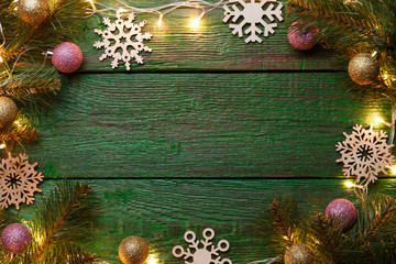 Photo of New Year's background with burning garland around perimeter, branches of spruce, Christmas balls, snowflakes