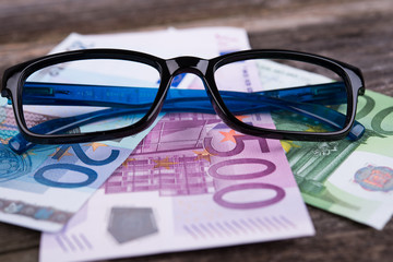 glasses frame with money on wooden ground