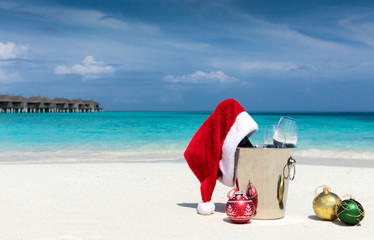 Sekt Kübel mit Weihnachtsmütze und Christbaumkugeln am tropischen Strand auf den Malediven