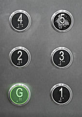 Generic series of metal elevator buttons shot straight on.