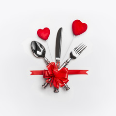 Festive table place setting with cutlery and red bow and two hearts on white background. Layout for Valentines day dinner invitation or anniversary, banquet, celebration, event