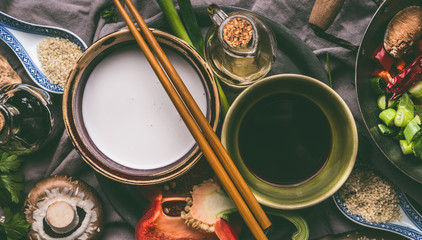 Bowls with coconut milk, soy sauce, sesame oil, chopsticks and vegetables on kitchen table background, top view.  Asian food cooking ingredients, Chinese or Thai cuisine concept