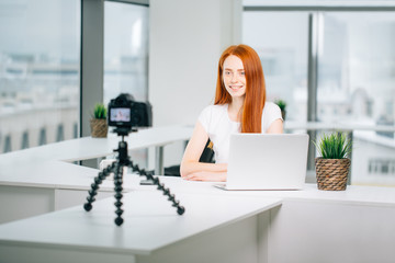 Young woman recording video on camera mounted on tripod for her vlog