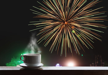 Cup of hot drinks on wooden desk with celebrate fireworks on night sky