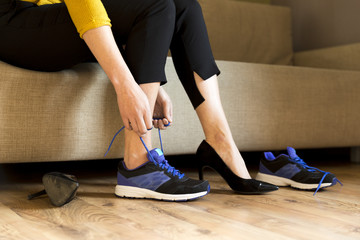 Woman changing high heels, office shoes after working day while sitting on the couch, ready to take a walk or run