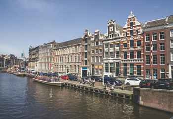 Traditional old buildings and boats in Amsterdam, Netherlands. Canals of Amsterdam.