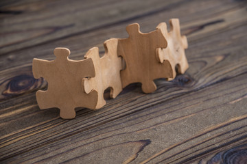 Placing a piece of the puzzle in a row on a textured rustic wooden table. Conceptual work in the team and cooperation.