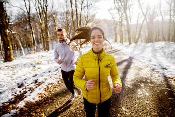 Smiling beautiful young healthy girl running with a trainer in sportswear through the forest in the sunny winter morning.