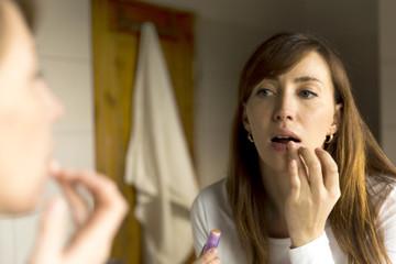 Lips care. Woman applying balsam on lips in bathroom