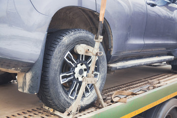 Tow truck towing a car. Car wheel close up with selective focus. Parking penalty charge concept.