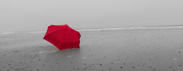 Roter Regenschirm am Strand