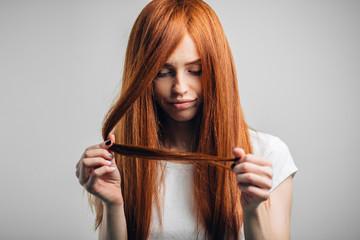 Sad redhead girl looking at her damaged hair.