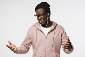 Horizontal shot of young handsome African guy isolated on white background wearing casual clothes and black hat listening to music and dancing with earphones on having closed eyes with delight