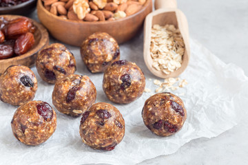 Healthy energy balls with cranberries, nuts, dates and rolled oats on parchment, horizontal, copy space