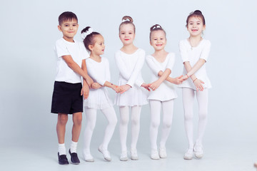 Little ballerinas and kid ballerun doing exercises and sitting on floor in white ballet class.