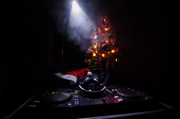 Dj mixer with headphones on dark nightclub background with Christmas tree New Year Eve. Close up view of New Year elements or symbols (Santa Clause, Snowman, Dog 2018, gift box) on a Dj table. toned