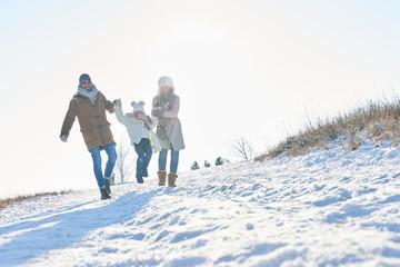 Glückliche Familie geht im Schnee spazieren