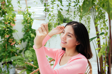 Cute asian girl is taking selfie photos and sitting in sunny garden.