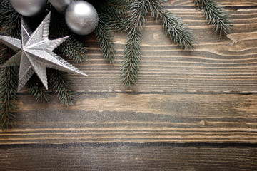 Christmas background with decorations, snow and fir tree on wooden board