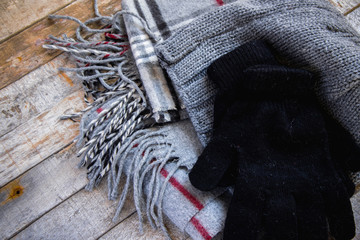 Detail of winter woolen accessory - hat, gloves and scarf on wooden background. Cozy autumn-winter concept