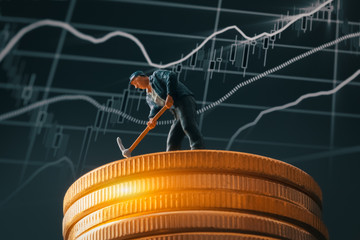 macro miner figurine on shiny bitcoin stack over stock market chart background