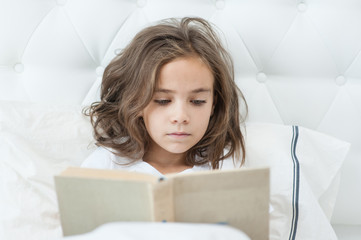 Little girl is reading a book in bed
