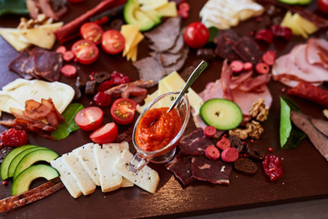 different cold appetizers cheese and meat on a wooden table
