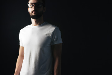 Young bearded hipster in glasses wearing in white blank t-shirt with a shadow on his face on dark background