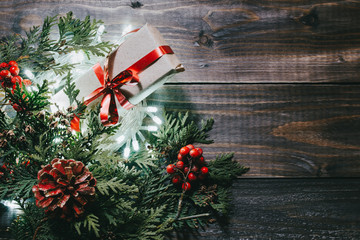 Christmas holiday flat lay view background. Xmas vintage above wooden table with gift box. Light garland