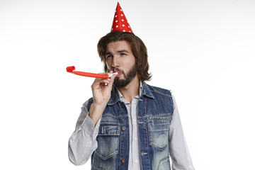 Isolated shot of attractive bearded hipster guy with red holiday cap on his head blowing whistle while celebrating birthday of his little sister. Cheerful joyful young male having fun on party