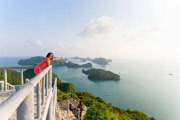 Woman tourist on the balcony is peak view point of Ko Wua Ta Lap island and beautiful nature landscape during sunrise over the sea in Mu Ko Ang Thong National Park, Surat Thani, Thailand