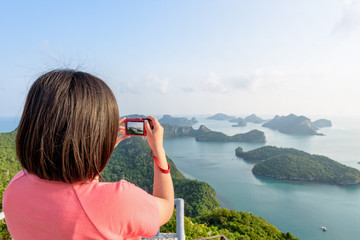 Woman tourist on peak viewpoint of Ko Wua Ta Lap island use camera take photos at beautiful nature landscape during sunrise over the sea in Mu Ko Ang Thong National Marine Park, Surat Thani, Thailand