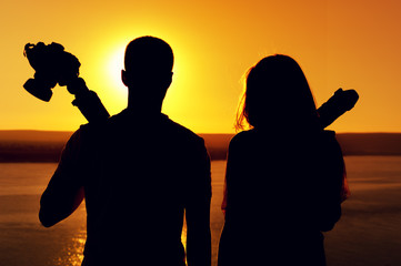 Rear view - silhouettes of young romantic couple - photographers standing together with cameras and tripod against background of sea surface on warm sunny day during sunset