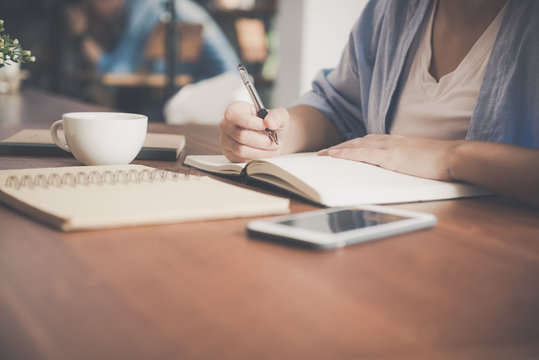 Young business woman in white dress sitting at table in cafe and writing in notebook. Asian woman talking smartphone and cup of coffee. Freelancer working in coffee shop. Vintage effect style pictures
