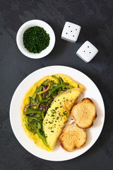 Omelette with green bell pepper and red onion sprinkled with chives, served on plate with toasted and buttered bread slices, photographed overhead on slate with natural light