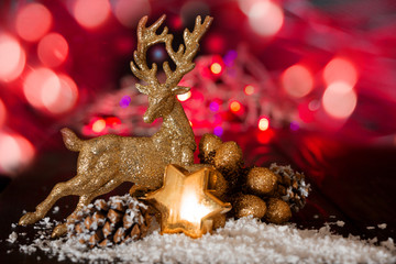 Christmas greeting card-golden deer, star, snow  and decoration on background of    red lights