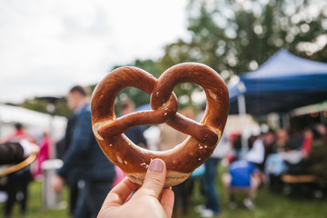 Celebration of the famous German beer festival Oktoberfest. The person holds in his hand a traditional pretzel called Brezel in the background of a blurry people.