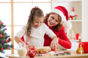 Mother and child daughter making christmas cookies and having fun. Focus on mother