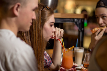 Young woman drinking milkshake while sitting with friends at cafe.