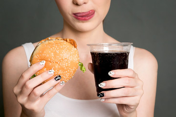 Young woman eating hamburger and cola on gray background. Junk food and fast food concept