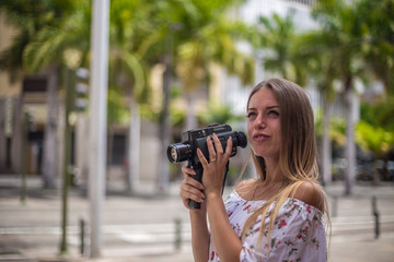 Tenerife. Spain. Cute blonde girl is observing and  filming streets in Santa Cruz de Tenerife. Girl travels concept. Travel to Canary Islands.