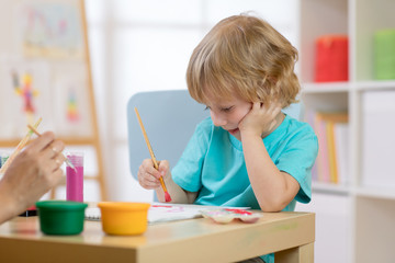 Portrait of little boy drawing something for art class