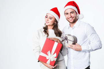 Young couple at Christmas in Santa Claus hats with gifts.