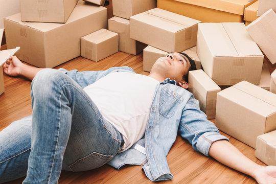 Man working overload and sleep near cardboard boxes around