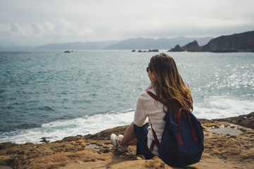 Female Traveler sitting and looking on sea waves
