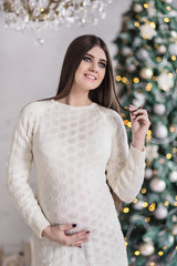 Pregnant woman in knitted dress opens gift near christmas tree