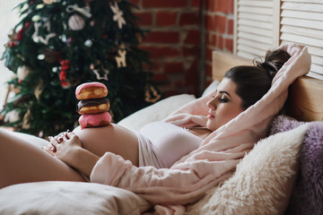 Pregnant woman lays in bed and eats doughnut