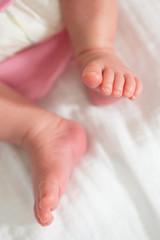 Baby girl legs on white blanket